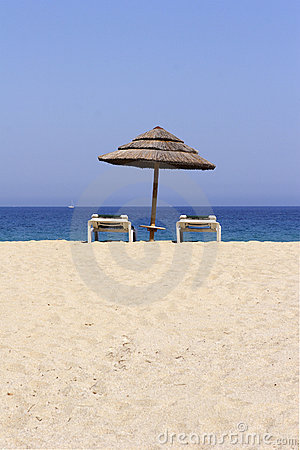 Sun lounger on empty sandy beach