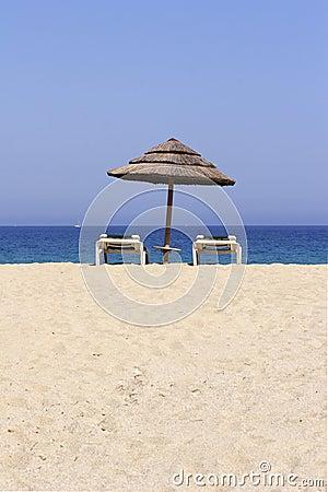 Sun lounger on empty sandy beach