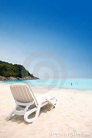 Sun lounger on sandy beach against blue sky