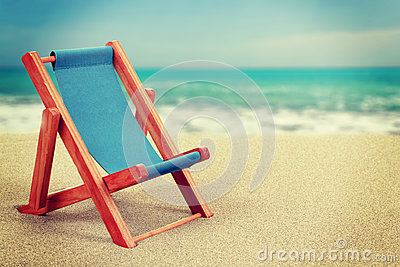 Sun lounger in sandy beach vintage toned