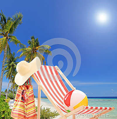 Sun lounger at sunny day on a tropical beach with palms