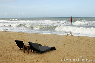 Sun loungers by rough sea