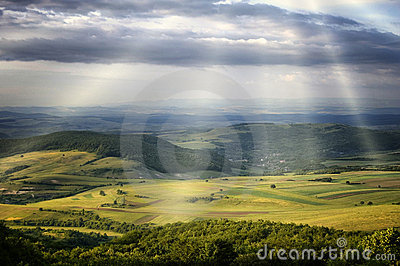 Sun rays over green hills