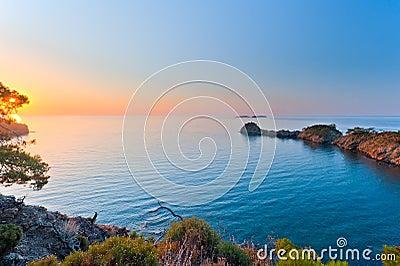 Sun rising over a calm sea in the bay