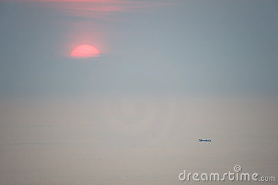 Sun rising over vast ocean