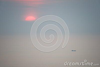 Sun rising over vast ocean