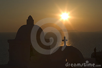 The sun sets behind one of the many Orthodox churches in the town of Fira, Santorini