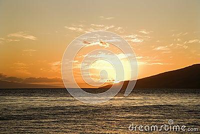 Sun setting behind island.