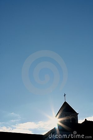 Sun shining behind church