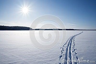 Sun, snow and Ski track crossing a frozen lake