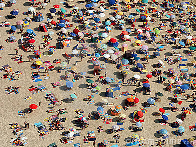 Sun umbrellas on a crowded beach