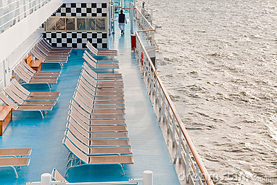 Sunbath chairs on side of cruise liner at morning