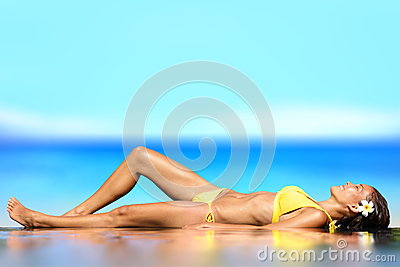 Sunbathing woman relaxing under sun in luxury