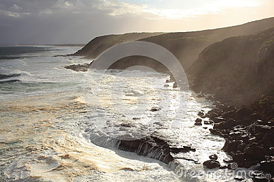 Stormy sea at coast with rays of sunlight