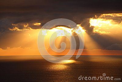 Sunbeams through dark clouds over ocean