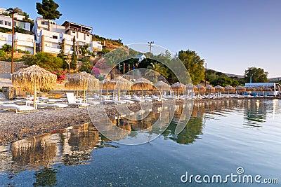 Sunbeds med ett slags solskydd på den Mirabello fjärden på Crete