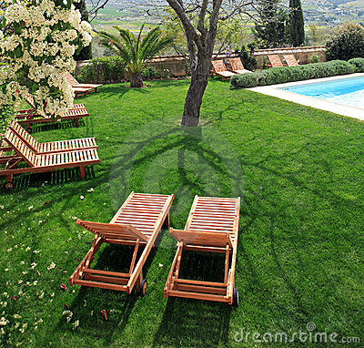 Free Sunbeds Next To A Swimming Pool In Garden Royalty Free Stock Images - 678759