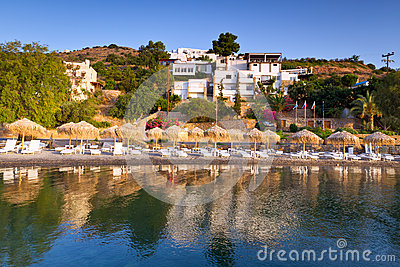 Sunbeds with parasols at Mirabello Bay