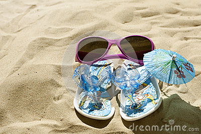 Sunglasses and sandals on beach