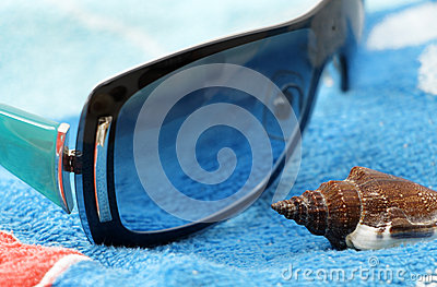 Sunglasses and seashell on a beach towel