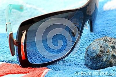 Sunglasses and seashell on a beach towel