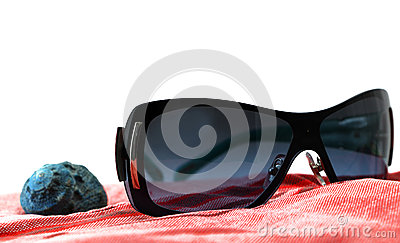 Sunglasses and seashell on a red beach towel