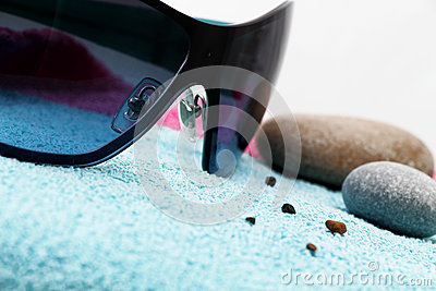 Sunglasses and shingle on a beach towel