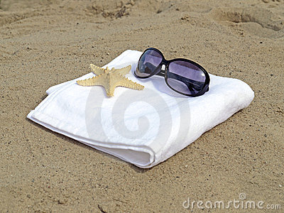 Sunglasses and starfish on white towel