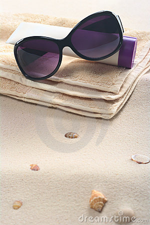 Free Sunglasses, Sunscreen And Towel On Sand Stock Photography - 19842222