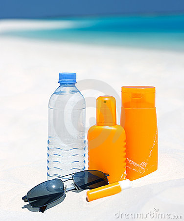 Sunglasses, water and sun protection cream on beac