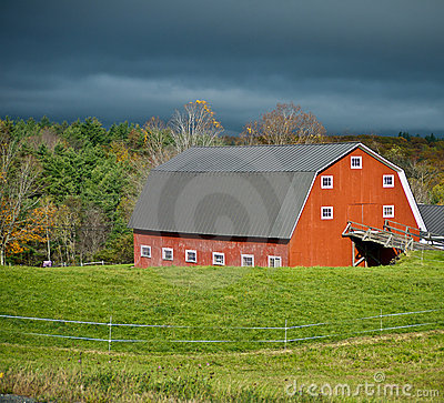 Sunlit Red Barn and Stormy Skies