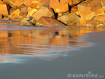 Sunlit rocks on sandy beach