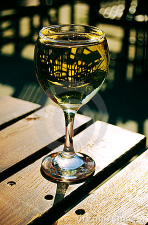 Sunlit white wine glass on a wooden table