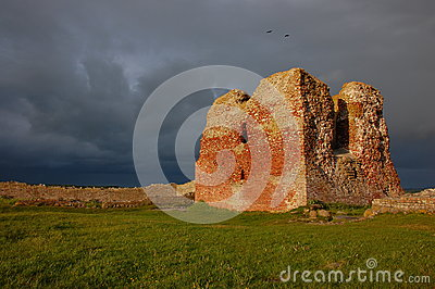 Sunny ruin tower under dark skies