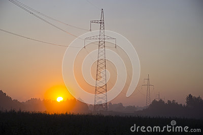 Sunrise and electric power stations on field