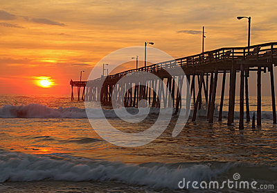 Sunrise by a fishing pier in north carolina royalty free for Nags head fishing pier