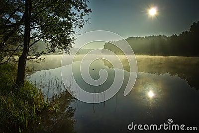 Sunrise at foggy lake