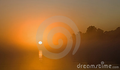 Sunrise on misty river