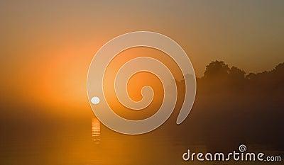 Sunrise on misty river
