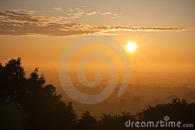 Sunrise over a hazy summer landscape