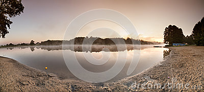 Sunrise over the misty lake panorama