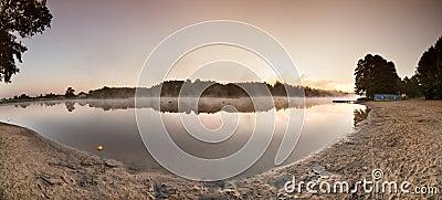 Sunrise over the misty lake panorama