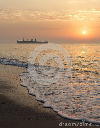 Sunrise at seaside with a shipwreck