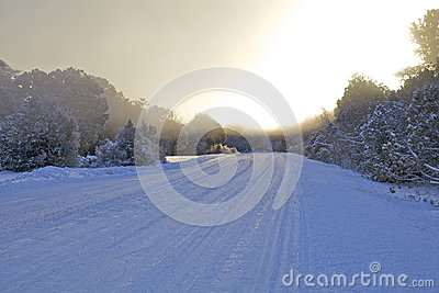 Sunrise on Snow Covered Road