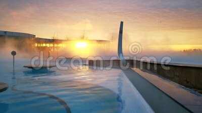Sunrise at the spa thermal water. Hydromassage thermal pool and steam above the pool stock footage