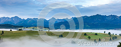 Sunrise and summer misty mountain country panorama