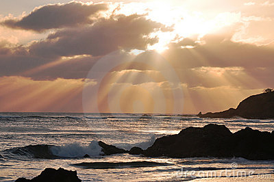 Sunrise with sunrays over rocky beach