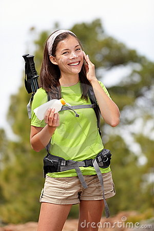 Sunscreen woman hiking applying sun lotion