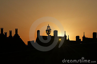 Sunset behind silhouetted roofs, London, England