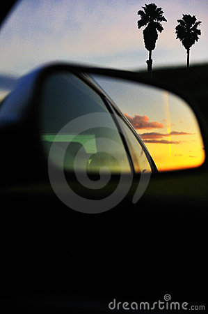 Sunset clouds reflected car mirror